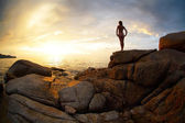 Woman standing on a rock and looking to the horizon over sea — Stock Photo