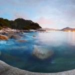 Panorama of a rocky coastline and motion blurred Andaman sea surface at twilight. Phuket, Thailand — Stock Photo #16284559