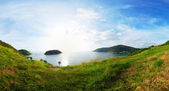 Panorama of tropical coast with island in calm blue sea. Nai Harn beach area of Phuket. Thailand — Stock Photo