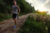 Young man with wet singlet running — Stock Photo