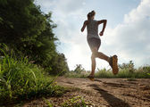 Young lady running on a rural road — Stock Photo