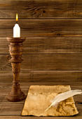 Feather, old paper and candle — Stock Photo