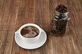 Cup of coffee and grain in a jar — Stock Photo