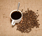 Cup of coffee and grain — Stock Photo