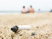 Cigarette butt on a beach — ストック写真