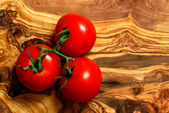 Pomidory na deski drewno oliwne — Zdjęcie stockowe