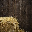 Bale of straw and wooden background — Stok fotoğraf