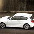 Stockfoto: White hatchback car parked in street