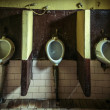 Three dirty urinals — Stock Photo