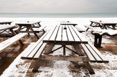 Wooden tables covered by snow — Stock Photo