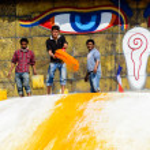 Man throwing orange paint on Boudhanath stupa — Stock Photo #39743893