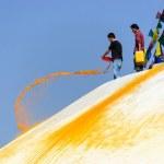 Man throwing orange paint on Boudhanath stupa — Stock Photo #39744303