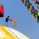 Man throwing orange paint on Boudhanath stupa — Stock Photo #39744473