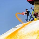 Man throwing orange paint on Boudhanath stupa — Stock Photo #39746355