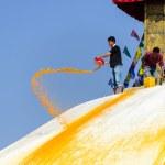 Man throwing orange paint on Boudhanath stupa — Stock Photo #39746429