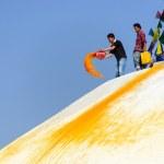 Man throwing orange paint on Boudhanath stupa — Stock Photo #39746497