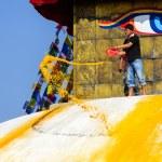 Man throwing orange paint on Boudhanath stupa — Stock Photo #39746505
