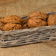 Foto Stock: Walnuts in wicker basket on sacking