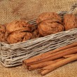Walnuts in wicker basket and cinnamon on sacking — Stock Photo #17040121