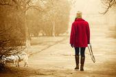 Chica con un abrigo rojo brillante paseando por el parque con un perro en una cl — Foto de Stock