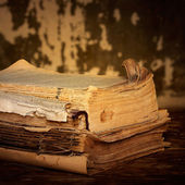 Dilapidated books on a wooden surface, sepia — Stock Photo