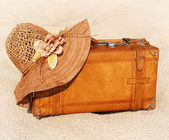Suitcase and straw hat on a sea-shore — Stock Photo