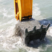 Excavator bucket of water picks up soil from the seabed — Stock Photo