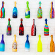 Bright decorative bottles hanging on a white brick wall — Stock Photo