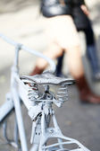 Detail of a Vintage Bicycle Saddle with a beautiful bokeh. Pedestrians on the street — Stock Photo
