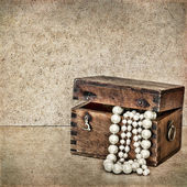Wooden chest with jewels and pearls on vintage background — Stock Photo