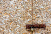 Metal lock on an abstract background compressed wood chippings b — Stock Photo