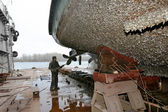 Work in dry dock with water jet cleans the bottom of the ship fr — Stock Photo