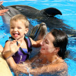 Happy beautiful young woman with a small child laughs and swims — Stock Photo #46402329