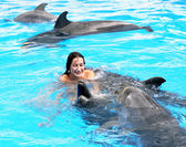 Happy beautiful young girl laughs and swims with dolphins in blu — Stock Photo