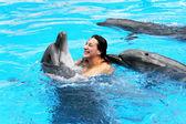 Gelukkig mooie meisje lacht en zwemt met dolfijnen in blu — Stockfoto