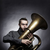 Portrait of a young man playing on the golden tuba — Stock Photo