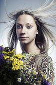 The beautiful young woman with a bouquet of wild flowers in hands — Stock Photo
