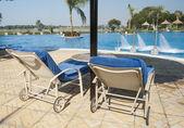 Chaises longues à côté de la piscine tropicale — Photo