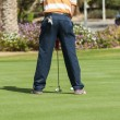 Golfer practising putting - Stock Photo