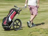 Golfer walking on course with bag — Stock Photo