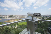 Binoculars on an aerial viewing platform over city — Stock Photo