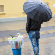 Man selling umbrellas stood in street — Stock Photo