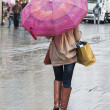 Woman with umbrella walking down street — Stock Photo #35494949