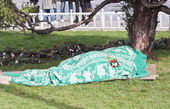 Homeless person sleeping under blanket in park — Stock Photo