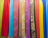 Row of scarves hanging in shop — Stock Photo