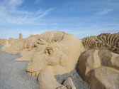 Large sand sculpture of a dinosaur — Foto de Stock