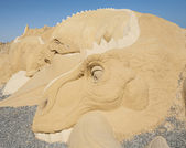 Large sand sculpture statue of a dinosaur — Stock Photo