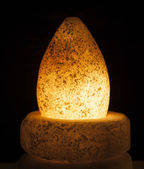 Ornate rock salt lamp on black background — Stock Photo