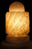 Ornate rock salt lamp on black background — Stock Photo