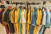 Row of tshirts hanging on a rail — Stock Photo